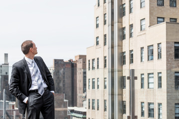 Young businessman standing in business suit looking up at New York City cityscape skyline in midtown Manhattan after interview break at skyscrapers rooftop