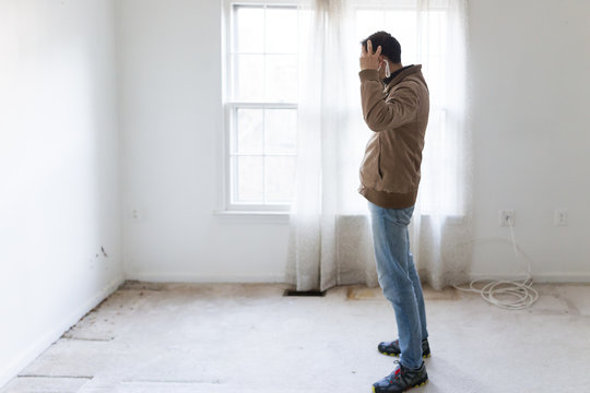 Young man in mask standing looking at room wall carpet floor flooring, white painted walls, during remodeling renovation, cleaning, inspection of dirty mold, dust, trash in corner