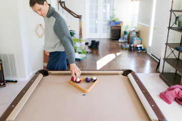 Interior inside house home with billiard pool table in living room, young man in winter cold sweater placing balls, setting up game, triangle