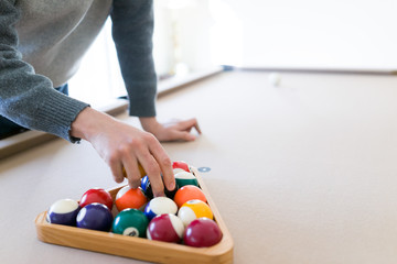 Interior house home with billiard pool table in living room, order of 15 balls inside triangle rack, setting up eight ball game