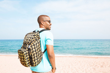 Portrait of attractive young African-American hipster wearing t-shirt and sunglasses walking at summer day on the beach with backpack