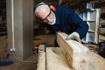 Senior master carpenter working in his woodwork or workshop.