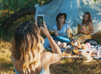 Group of girls friends making picnic outdoor. They make photo from smartphone