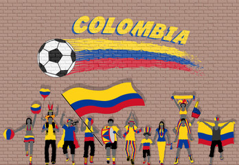 Colombian football fans cheering with Colombia flag colors in front of soccer ball graffiti