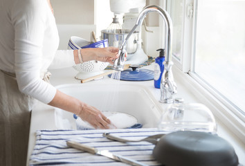 Photograph of a woman's hands washing dishes in a white kitchen with blue accents