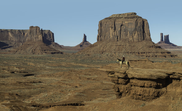 A man on horseback overlooks from John Ford's Point in Monument Valley, Arizona