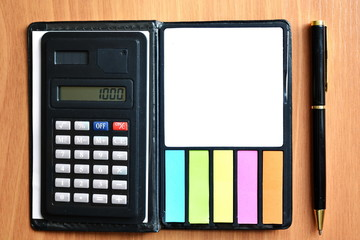 Black digital office calculator with solar panel and notebook with color sticker and empty white paper blank for note next ballpoint pen on wooden table. Top view