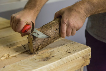 Carving a piece of pine with a sharp knife