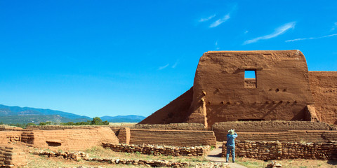 A tourist photographs the historic church at Pecos National Historical Park in New Mexico