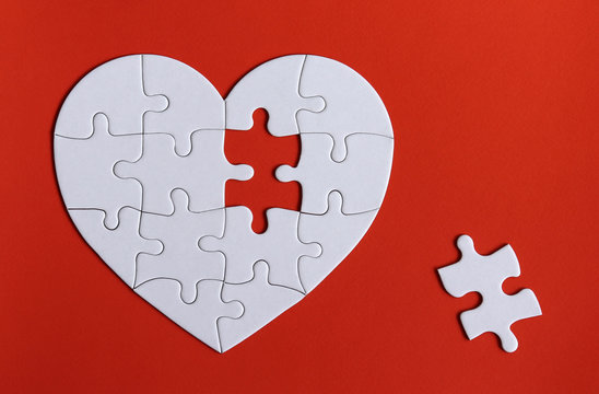 A missing piece of the puzzle and puzzles in the shape of a white heart on the red background.