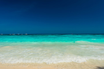 Wall Mural - Beautiful water spalsh and bright water at the tropical beach with blue sky