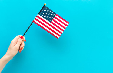 Woman's hand holding small american flag on blue background. Space for text.