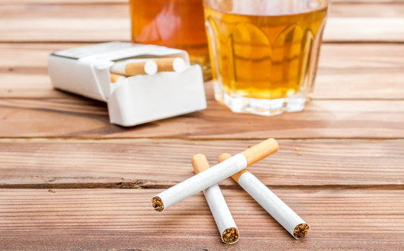Cigarettes with alcohol drinks on wooden table. Social issues.