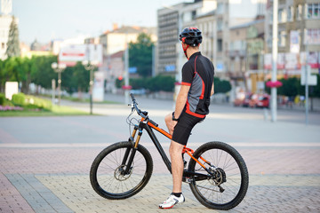 Back view of athletic male bicyclist resting on bicycle after hard race. Sportsman taking break after morning outdoor activities riding bike. Concept of healthy lifestyle, exercising on fresh air