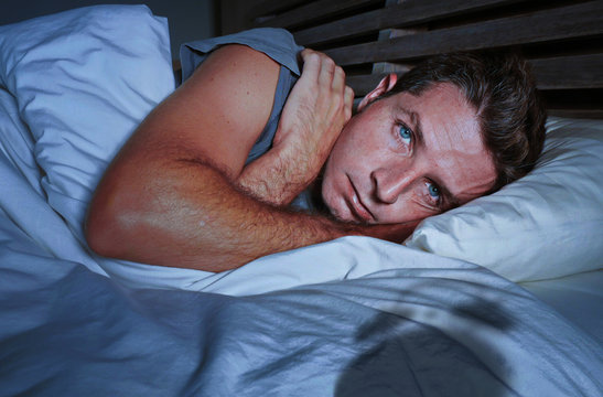 restless worried young attractive man awake at night lying on bed sleepless having eyes opened depressed suffering insomnia sleeping disorder