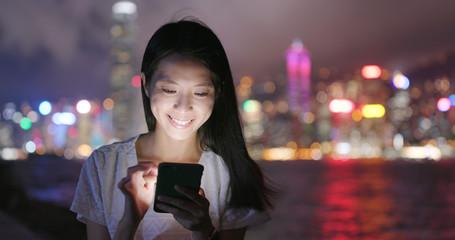 Wall Mural - Woman use of mobile phone in Hong Kong at night