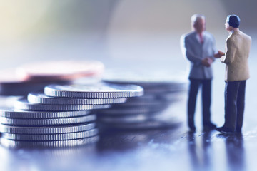 Double exposure row of coins of Two Business man and graph,saving,investment and finance concepts. Miniature people Stand in front of a coin,soft focus and blurred style.