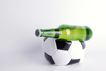 One deflated soccer ball and bottle of beer