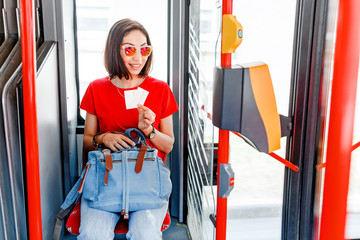 Woman sitting in bus and her showing tickets