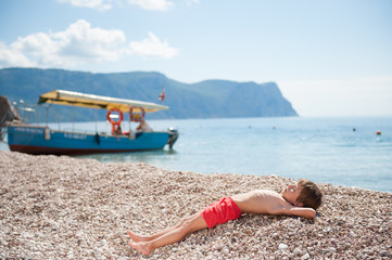 healthy little kid lying on summer beach on sea with wooden boat background