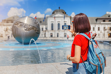 Happy tourist woman doing selfie and photographing palace residence of President and fountain with globe. Travel in Bratislava and Slovakia concept