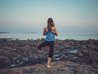 Woman in yoga pose on the coast at sunset