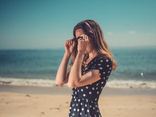 Woman on beach putting on sunglasses