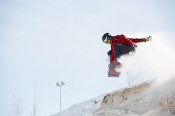 Photo of man with snowboard jumping from snowy mountain slope