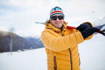 Image of smiling man with mountain skis