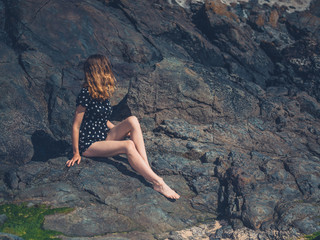 Woman sitting on rocks in summer