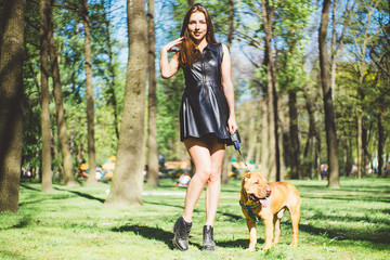 A beautiful girl is walking with a sharpei dog