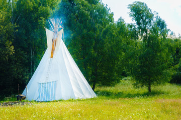 white teepee indian tent standing in beautiful summer landscape.