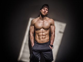 Attractive shirtless blond male bodybuilder in shorts indoors in dark gym, showing muscular torso and ripped abs
