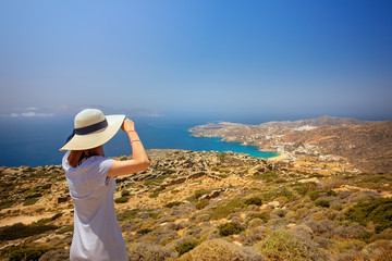 Woman on a top of a hill looking towards a beach, Greece, Cyclades.