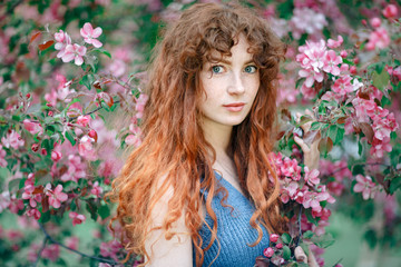 Summer portrait of young tender girl, ginder hair, redhead young girl with freckled skin. Caucasian girl posing in flowers