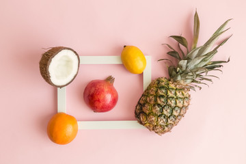 Exotic fruits around photo frame on rose background abstract.