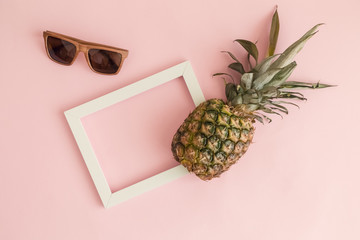 Pineapple, photo frame and wooden sunglasses tropical abstract concept.