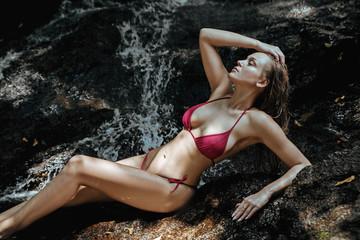 Sensual blonde relaxing in a waterfall