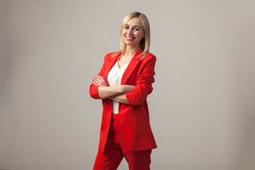 Young beautiful white blond girl in a bright red strict suit with a jacket and white blouse standing in a pose on a white isolated background