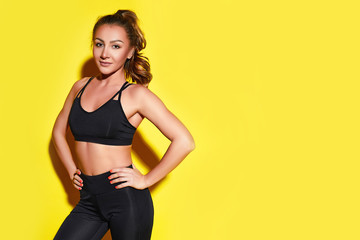 Young happy fitness girl with sporty body posing at studio on a yellow background. Beautiful fit Girl. Fitness smiling model in black sportswear. Weight Loss. Sporty healthy female. Horizontal