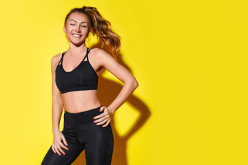 Young happy fitness girl with sporty body posing at studio on a yellow background. Beautiful fit...