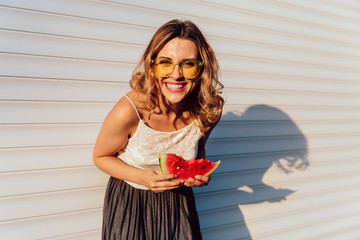 Excited girl, cheerfully smiling while looking at camera and eating a watermelon, wearing stylish clothes, yellow sunglasses, posing against the white wall, outdoors.