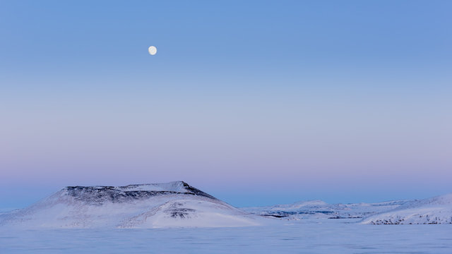Full moon over snow covered volcanic craters at sunset