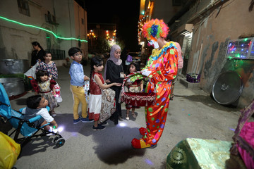 Man dressed as a clown gives candies to children as they celebrate Gargaoon in Darin, Dammam