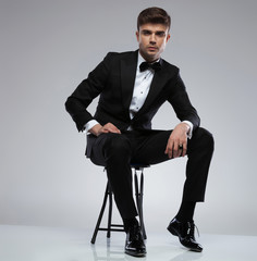 sexy confident man wearing a black tuxedo sitting