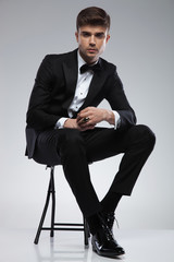 attractive seated stylish man in black tuxedo and black bowtie