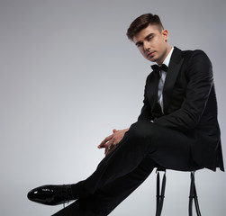sexy elegant man in black tuxedo sitting on metal chair