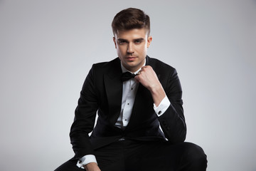 portrait of seated young businessman in tuxedo fixing his bowtie