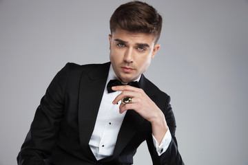 sexy businessman wearing black tuxedo with golden ring on finger