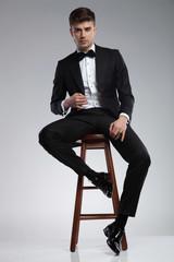 sexy elegant man in black tuxedo sitting on wooden chair